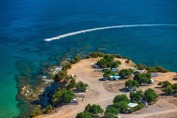 The coastline of the azure sea, a camp located on the shore with trailers and tents, a boat passing near the shore, towing water sledges. Camping in Akamas National Park, Cyprus.