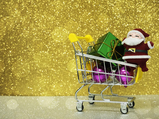 Closeup Christmas shopping cart with colorful gift boxes on blurry and dreamy bokeh gold and black background with copy space, holiday shopping concept