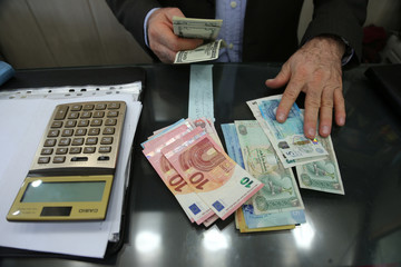 Money changer holds U.S. dollar banknotes as he counts other currency banknotes at Grand Bazaar in Tehran