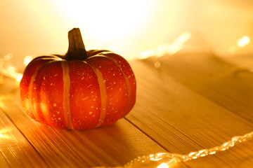 Pumpkins and lights decorate the halloween day on the wooden floor.