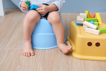 Closeup of legs of cute little Asian 18 months old toddler baby boy child sitting on potty playing with wooden blocks toy