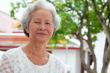 Older Asian women with grayish hair have smiling faces.