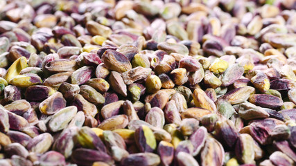 Colorful background with a lots of roasted riped green and brown pistachios