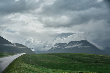 Travel to Iceland. A mountain road with fog to the town of Isafjordur and a view of the fjord after rain. focus on the road