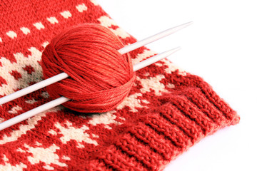Set for knitting, knitting needles, a red coil of wool and a knitted sweater on a white background.