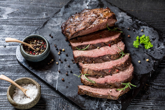 Sliced grilled roast beef with salt and pepper on marble plate on wooden old rustic table Black background.