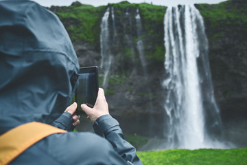 Girl in waterproof clothing stands under the Seljalandsfoss waterfall in Iceland. back view, woman with small orange backpack take a photo on smartphone