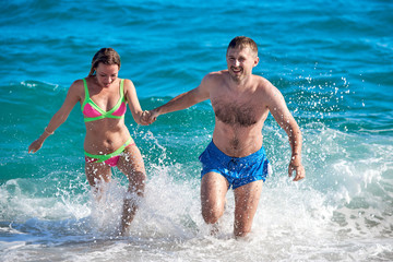 Caucasian man and woman getting out from the sea water. Front view.