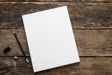 Empty white canvas frame with pencil on a wooden background.