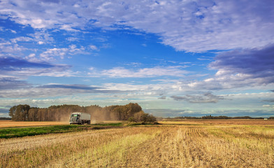 A semi truck and trailer driving down a dirt road between harvested fields in a afternoon autumn cloudy countryside landscape