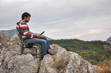 Man sitting and reading on the edge of a cliff surrounded by nature. Concept of peace in nature