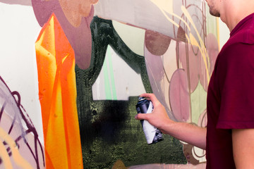 Artists draw graffiti on a fence.