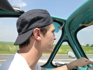 Young man driving heinkel cabin (vintage car) in turquoise 2