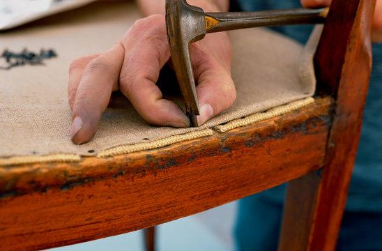 a upholsterer repairs an antique chair