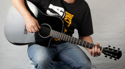 Music - Man play a black electric acoustic guitar
