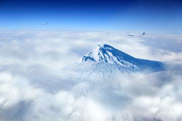 Obraz Samoloty pasażerskie i szczyt góry nad chmurami. - fototapety do salonu