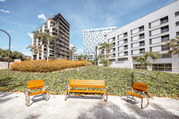 Fototapete - View on the garden with benches at the modern office disstrict in Barcelona city