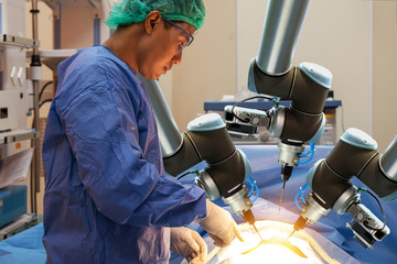 Smart precision healthcare technology , artificial intelligence concept. Automation robot hand machine in operating room and surgery doctors in futuristic hospital.