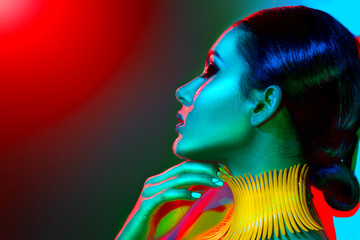 Foto op Canvas Beauty Fashion model woman in colorful bright lights with trendy make-up, manicure and haircut