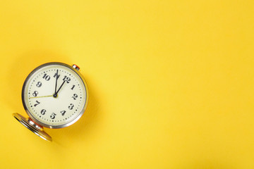 Vintage alarm clock on yellow background with copy space.