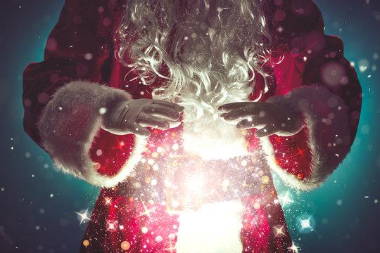 Santa Claus with magic Christmas lights