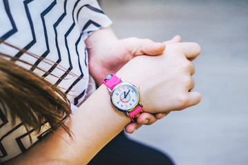 Girl looks time on her pink kidswatch.