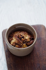 Baked muffin cake with cinnamon and brown sugar in a ceramic cake. White rustic wooden table