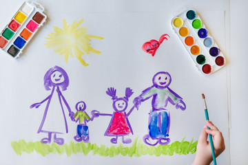 The child's hand paints a happy family