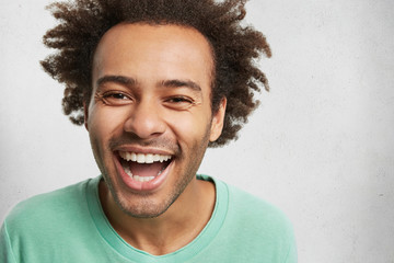 Overjoyed happy man with dark skin and bushy hairstyle, grins at camera, expresses positive emotions, laughs as hears anecdotes. Contented satisfied male model has good mood after noisy party