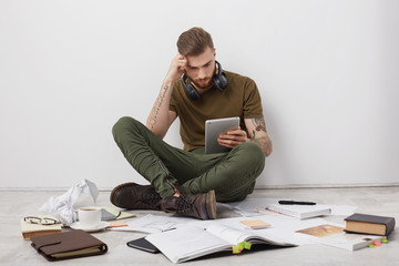 Concentrated stylish hipster guy with tattooed arms, sits crossed legs on floor, surrounded with many books and papers, holds tablet computer, searches information in internet for writing report
