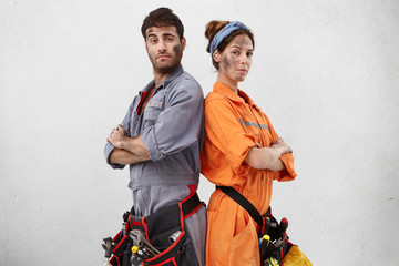 Portrait of confident handyman and his female colleague stand back to each other, keep hands folded, have dirty faces after repairing steps, wear special uniform and belt with tools. Maintenance Wall mural