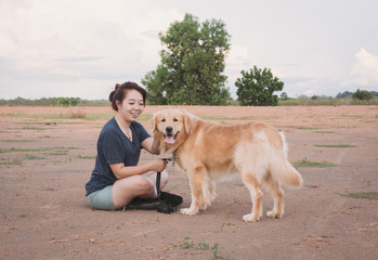 woman with her golden retriever dog playing outdoors