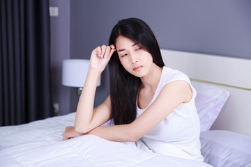 worried woman thinking on bed in bedroom