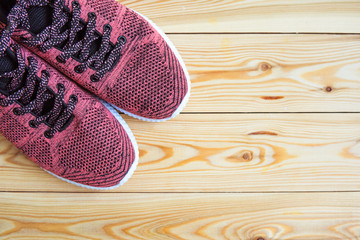 Sneakers pink on a wooden background top view