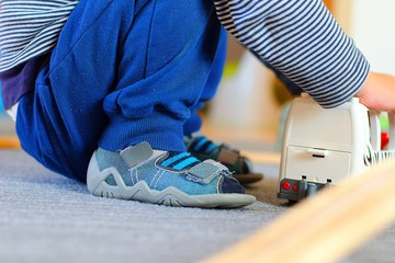Detail of children´s orthopedic shoe. Boy wearing arch supporting slippers at home.