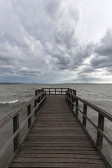 First person view of a pier on a lake on a moody day, with dark water and overcast, stormy sky