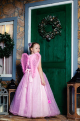Girl in angel costume knocking at the door