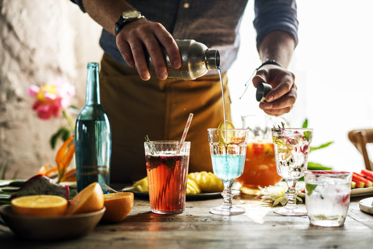 Bartender mixing colorful cocktails