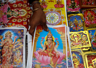 A vendor reach out for the poster of Goddess of Wealth Laxmi, kept on sale for the Tihar festival in Kathmandu