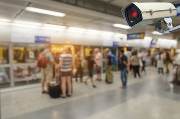 CCTV, security camera system operating with people waiting subway at train station, surveillance security and safety technology concept