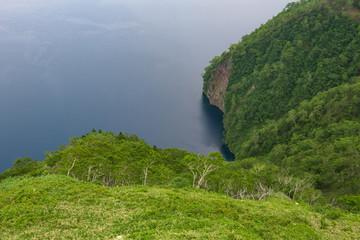 Green slopes surrounding the beautiful and deep blue Lake Mashu, Hokkaido, Japan