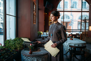 Serious dark hair lady stands near table