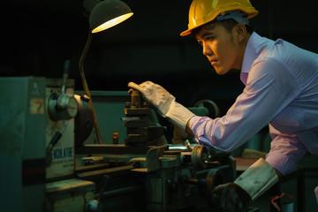Metal worker looking on Workpiece in workshop.