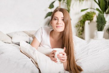 Happy girl  drinking coffee on bed in the morning in home