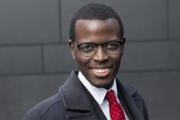 Horizontal headshot of dark-skinned African entrepreneur pictured against gray wall wearing formal clothes and black-rimmed eyeglasses looking confident and interested, smiling friendly at camera