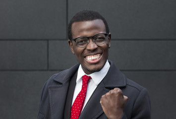 Horizontal closeup of African American businessman pictured against gray wall in formal clothes and glasses with gesture of content, glad about achieving long-awaited success in business deal