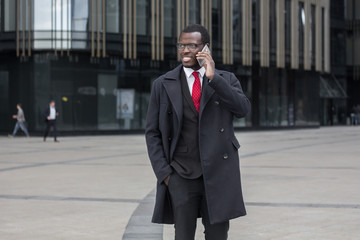 Outdoor image of young African American man moving from one office to another, standing in street in city center, having phone chat about crucial business matters, trying to find solution to problems