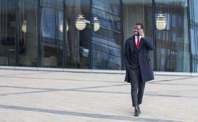 Full length image of African American guy walking outdoors in city center dressed in formal suit and coat, holding smartphone and having pleasant conversation about business or family issues, smiling