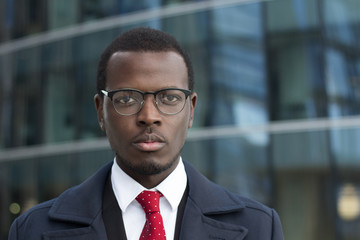 Urban headshot of handsome African businessman dressed in smart coat in city street wearing stylish eyeglasses, looking straight at camera with serious and concentrated face, focused on work