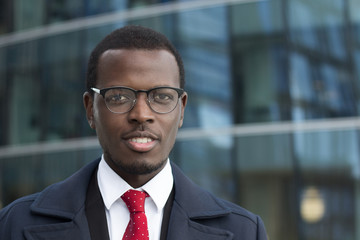 Outdoor closeup of African American entrepreneur pictured in street with high glass building in background, wearing black-rimmed eyeglasses, looking calm but concentrated on business matters